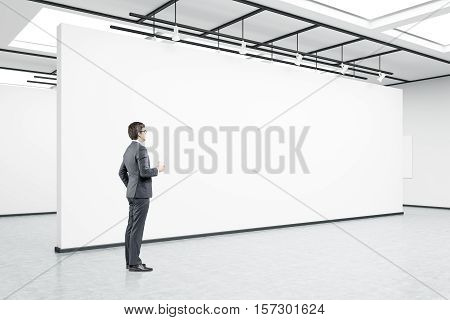 Side view of a man wearing glasses and holding a cup of coffee standing in an empty exhibition hall. 3d rendering. Mock up.