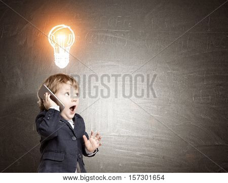 Little kid is talking on the phone standing near the blackboard with glowing light bulb sketch on it. Concept of a bright idea. Mock up