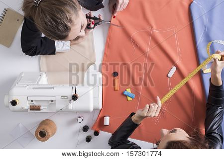 Top view of young women working at a tailor shop. One is cutting red tissue. The second is holding measuring tape
