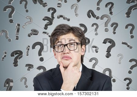 Close up of bespectacled young businessman thinking near a concrte wall with question marks falling. Concept of looking for the answer