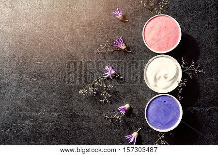 Purple spa setting on old black stone table - cream or mask in little cup with dry flowers around