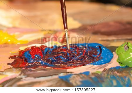 Acrylic colourful paint mixing on a pallet.