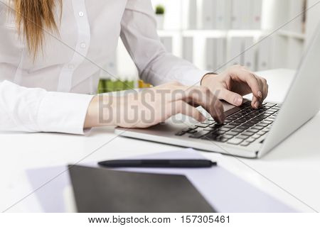 Close up of a red haired woman's hands with short nails who is typing in office at her laptop keyboard. Concept of secretary job