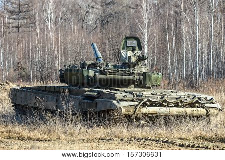 Russian tank t-72 rides on a forest road