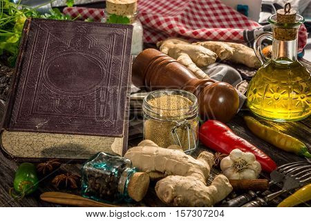 Old cook book with ingredients on wooden background