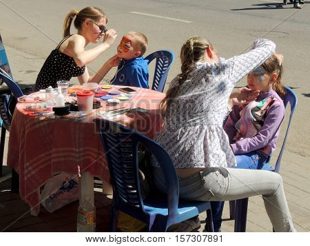 VORONEZH, RUSSIA - May 9, 2016: Two girls doing face painting elementary age girl and boy sitting in a chairs on a city street during the celebration in the City. May 9, 2016 in Voronezh, Russia