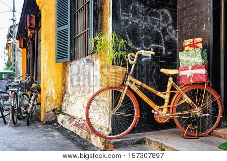 Handmade Bamboo Bicycle With Gift Boxes On Rack Parked Near Wall