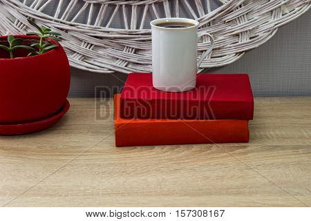 White Cup Of Tea And An Open Book On A Wooden Table. A Red Pot With Green Tree In The Background.