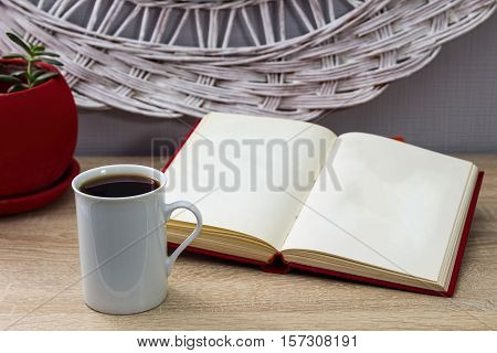 White cup of tea and an open book on a wooden table. A red pot with green tree in the background. Reading learning