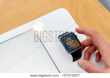 PARIS FRANCE - SEP 12 2016: Woman testing new Apple watch testing its functionalities before buying the latest smartwatch - testing new sport coach function bike velo