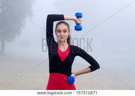 Young Sporty Woman Exercises With Dumbells During Fitness Training Outdoor