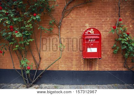 COPENHAGEN, DENMARK - JUNE 08, 2016: Sending a letter via red old style mail box in Copenhagen, Denmark on June 08, 2016.