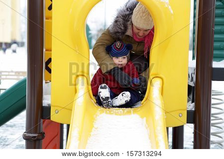 Toddler on a slide at playground in winter