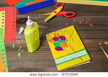 Craft making. Making a greeting card. Colored paper, applique, handmade. Scissors, glue, paint brush. Dark wood background. School supplies