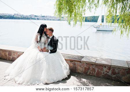Wonderful Wedding Couple Sitting On Bench Background Sailing Ship On Lake.