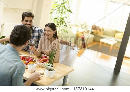 Group of happ young people sitting by the table eating and drinking red wine