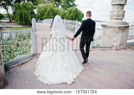 Back View Of Walking Wedding Couple At Bridge To Island Of Love.