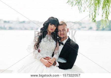 Wonderful Wedding Couple Sitting On Bench Background Lake.