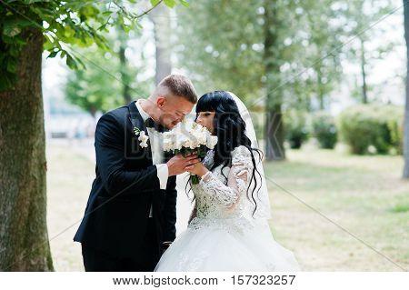Adorable Wedding Couple At Park Sniff Wedding Bouquet.
