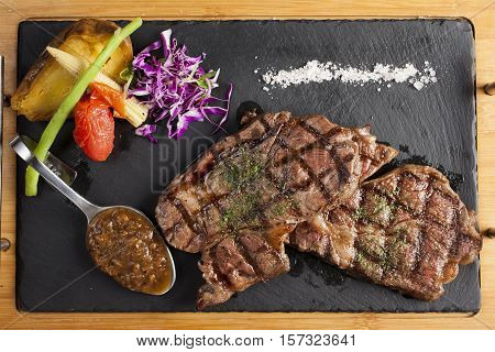 Beef rump steak on black stone table, direct abov