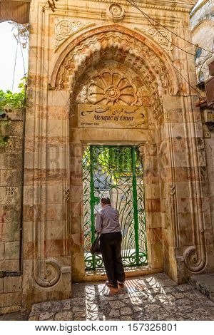 JERUSALEM, ISRAEL - JUNE 19, 2015: Man entering the green gate of the Omer mosque in old city.