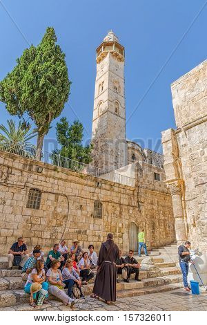 JERUSALEM, ISRAEL - JUNE 19, 2015: People resting in front of the Omer mosque minaret at the atrium of the Church of the Holy Sepulchre.