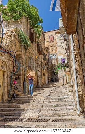 JERUSALEM, ISRAEL - JUNE 19, 2015: A boy carries a box coming down the staircase alley of the old town.