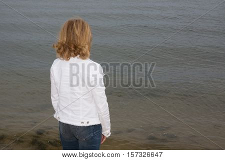 Lonely woman in white casual outfit with Blond hair sitting at beachfront