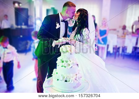Awesome Newlyweds On Wedding Party With Wedding Cake At Colourful Light And Heavy Smoke On Restauran