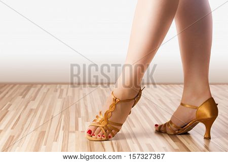 Female legs are in golden latin dance shoes.