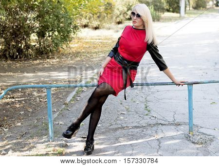 the blonde in a red dress sits on a protection in the park a subject beautiful women