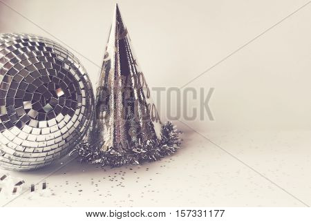 Silver disco ball, party hat and ribbon with open space for copy. New years eve background.