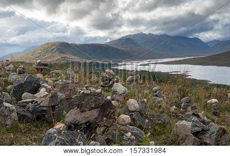 Inukshuks along the borders of Scottish Loch Ness overshadowed by dark clouds