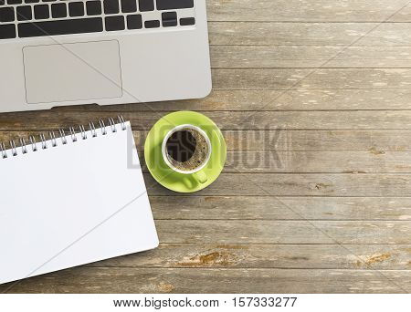 Blank paper notebook with laptop computer and cup of coffee on wooden table.View from above.Office supplies and gadgets on desk table.Working desk table concept.Writing notes.
