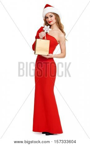 beautiful girl with shopping bag in red gown and santa hat isolated on white background, christmas holiday concept