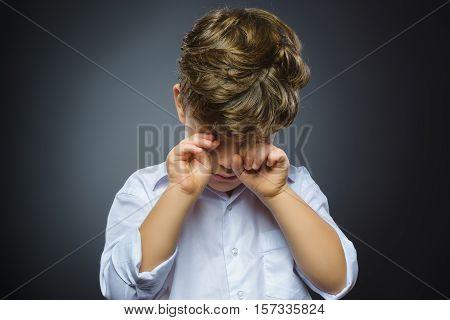 Closeup Portrait of crying boy with astonished expression while standing against grey background.