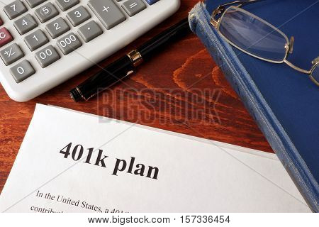 Papers with 401k plan and book on a table. poster