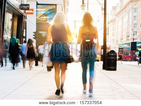 Blurred image of two young girls walking in Oxford street against of sunset. Oxford street one of the main shopping destination of London