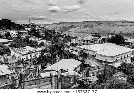 The Congolese town Matadi at the Congo river in black and white. The city is built over several hills with wildly varying architecture.