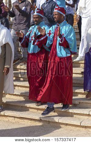 JERICHO, ISRAEL - NOV 12, 2016: Two male pilgrims in celebration clap at Qasr el Yahud while visiting the Baptismal site on Jordan river.