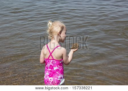 little blonde haired girl playing by the water