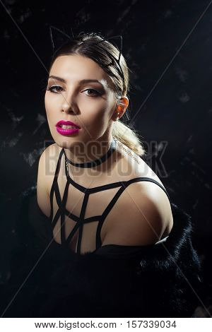 Gorgeous young woman in sensual modern black outfit and makeup. Closeup studio portrait of beautiful female Caucasian model in black on black background. Retouched, studio lighting.