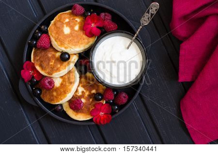 cheese pancakes with berries and yoghurt for breakfast