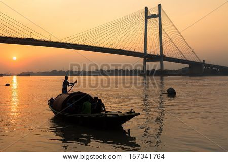 Wooden country boat on river Hooghly at sunset with Vidyasagar bridge at the backdrop (silhouette), These boats are used for pleasure boating on the river.