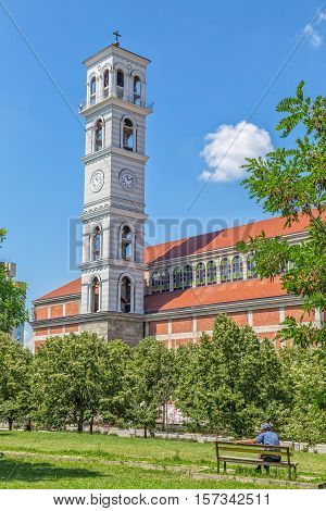 PRISTINA, KOSOVO - JULY 01, 2015: Clock tower and belfry of the Roman Catholic Cathedral of Blessed Mother Teresa view from the park in the city center.