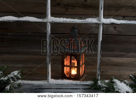Selective view of a glowing lantern through a snow covered window with fir branches.