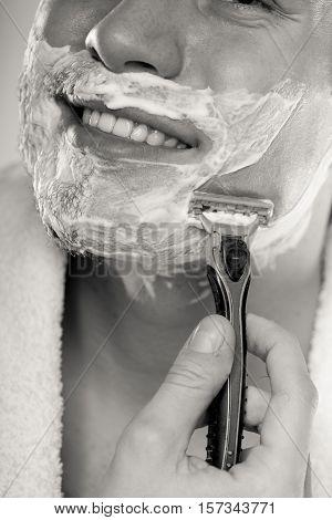 Man shaving using razor with cream foam. Guy removing face beard hair. Skin care and hygiene. Black and white bw photo.