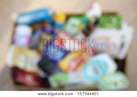 Blurred background of domestic recycling box with waste from major UK brands