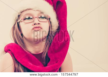 Christmas holiday concept. Toddler girl wearing Santa Claus hat and christmassy dress making funny face.