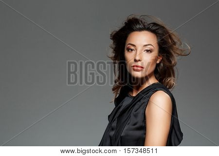 Young beautiful confident woman in black dress looking at  camera over grey background. Copy space.